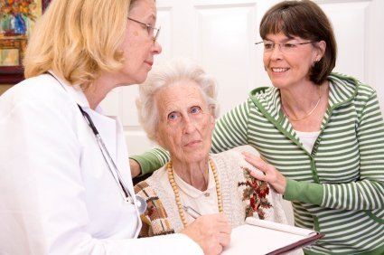 Senior woman visiting with her doctor and caregiver