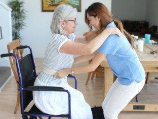 caregiver helping lady stand