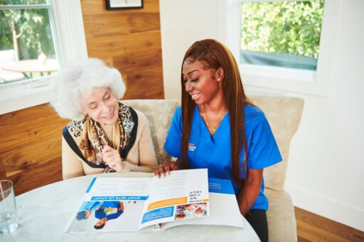 Caregiver and senior woman discuss in-home care funding sources